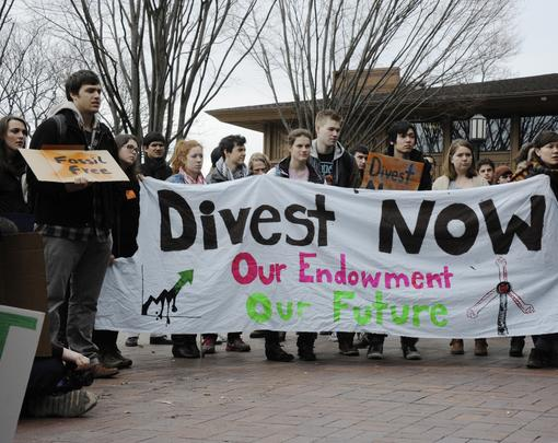 "Students standing behind a banner that reads ""Divest Now"""