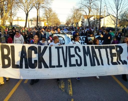 "A group of protestors marching behind a banner that reads ""Black Lives Matter"""