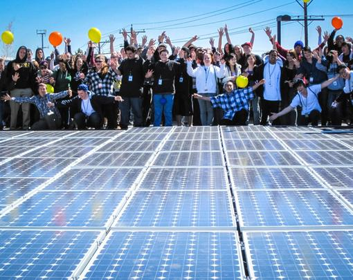 A large group of people celebrating a solar array