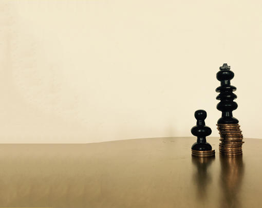 Two chess pieces, a king and a pawn, atop unequal stacks of coins.