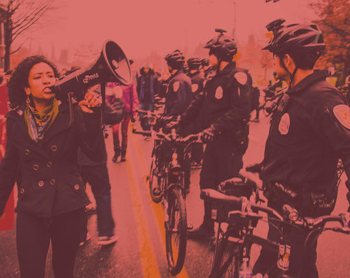 A women with a megaphone protests near a line of bicycle cops.