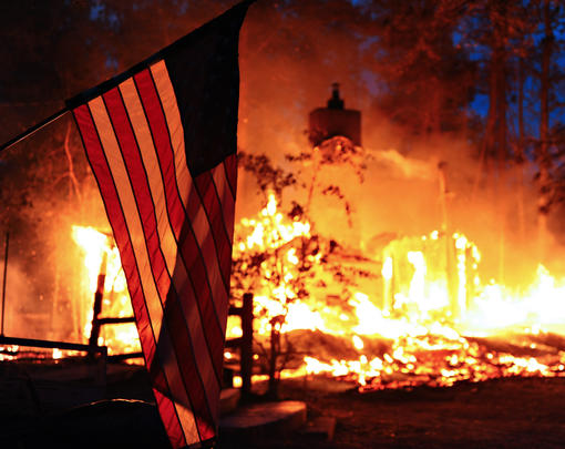 An American flag in front of a raging wildfire