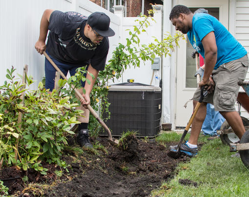 Two workers use shovels to create a rain garden