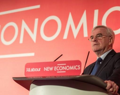 "John McDonnell at a podium in front of the word ""Economics"" on a red background."