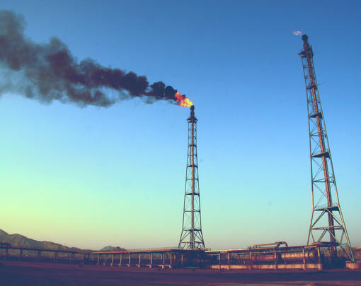 Two oil wells, one belching smoke and fire.