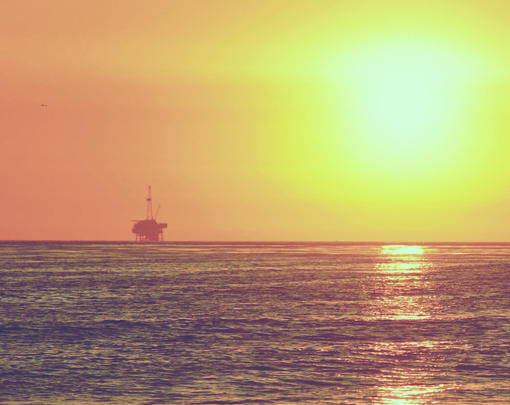 The sun setting with an ocean-based oil rig on the horizon