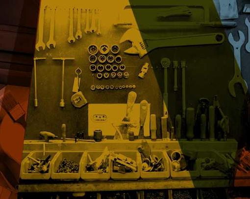 Tools are hung on a wall of a workshop with different colors overlapping over them.