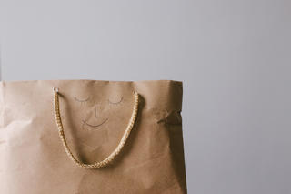 A shopping bag with a happy face drawn on it