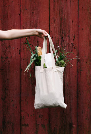 A cloth bag filled with unpackaged vegetables.