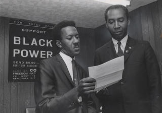 "Two CORE officials discuss a memo while standing in front of a sign in their office that reads ""Support Black Power"""