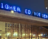"A glowing sign reading ""Higher Ed Not Debt"" above a university campus"