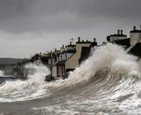 A storm surge pushing waves onto shore, threatening a row of houses.