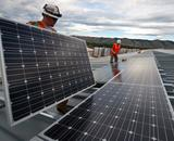 Men in hardhats installing solar panels
