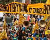 "Marchers beneath a banner that reads ""To Change Everything It Takes Everyone"""