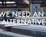 """We Need An Alternative"", on top of an image of a factory."
