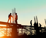 Construction workers erecting a large building against the dawn