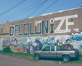 a wall is half covered in graffiti, in the top half, which is mostly unadorned, the word 'DECOLONIZE' is painted in large black and white letters