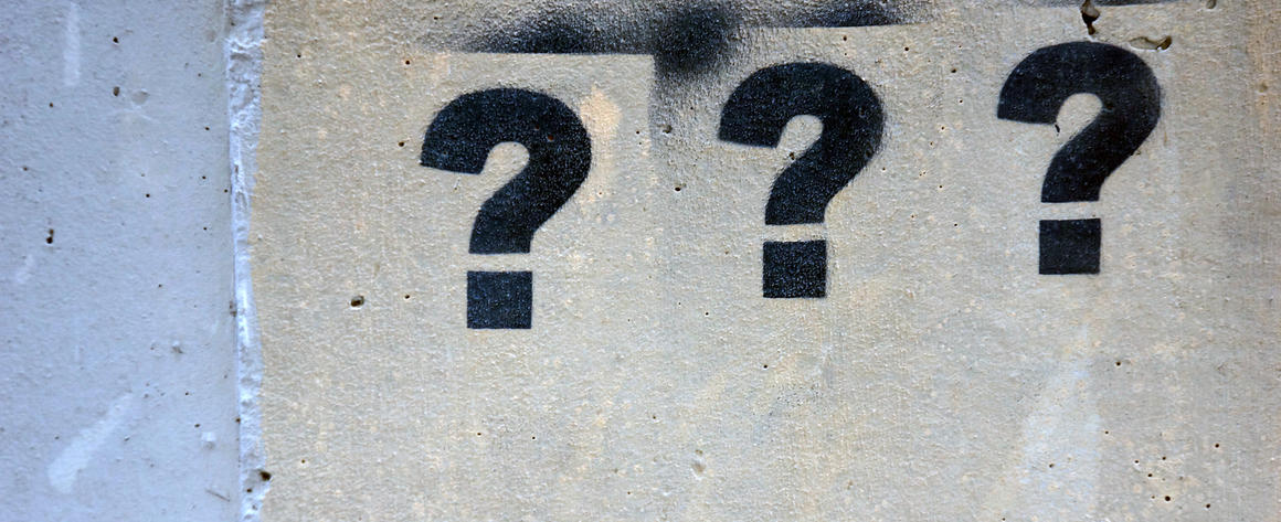A series of question marks stenciled on a wall.