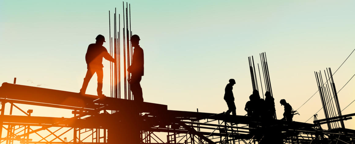 Silhouetted workers constructing a building