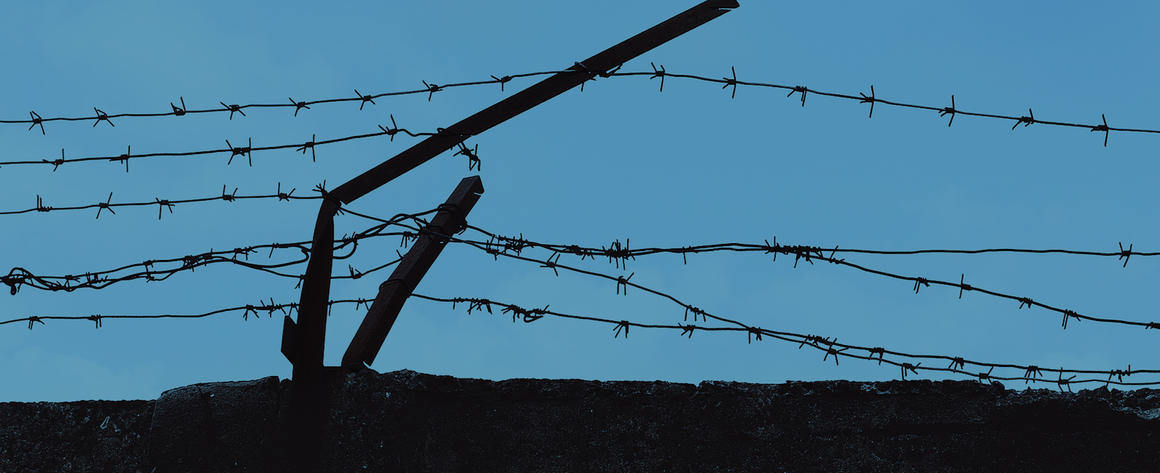 Strands of barbed wire on top of a wall, beginning to come apart.
