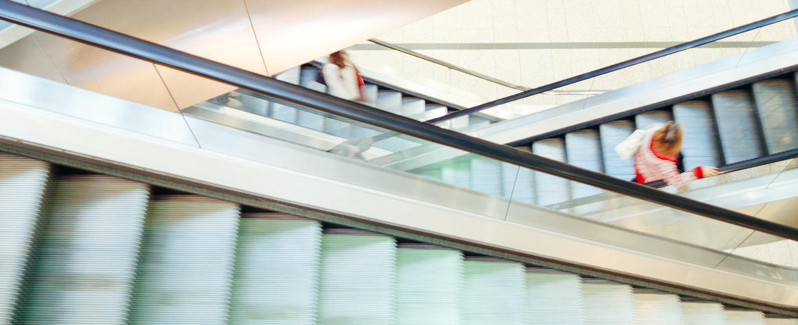 Crossing escalators in a shopping mall, with a solitary consumer.