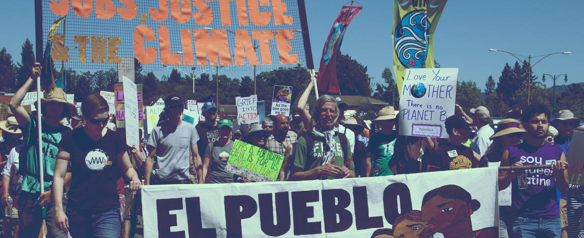 "Signs carried by marchers reading ""El Pueblo Unido"" and ""United for Jobs Justice and Climate"""